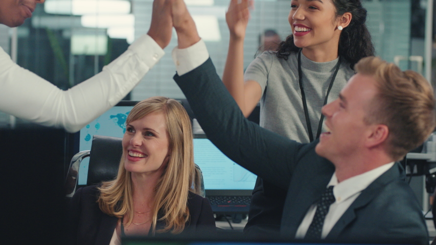 sales team celebrating success with high five looking at financial graph data on computer screen happy business people enjoying corporate victory achievement in office Royalty-Free Stock Footage #1034483216
