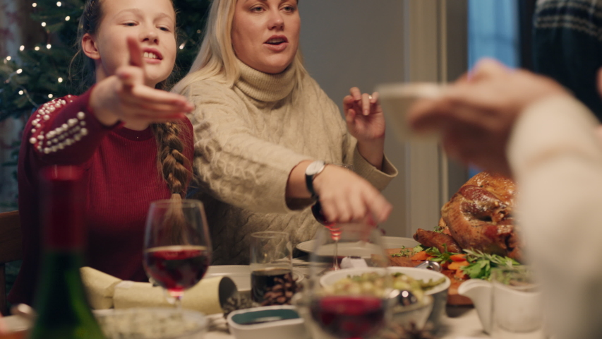 Happy family christmas dinner sharing delicious homemade meal at festive celebration sitting at table enjoying feast celebrating holiday at home with friends 4k footage | Shutterstock HD Video #1034495345