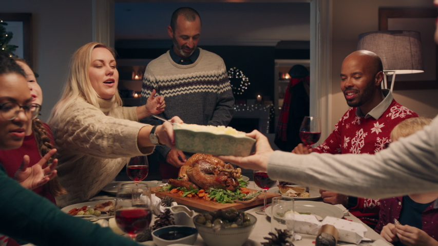 Family christmas dinner man cutting turkey serving delicious meal at festive celebration people sitting at table enjoying delicious feast celebrating holiday at home 4k footage