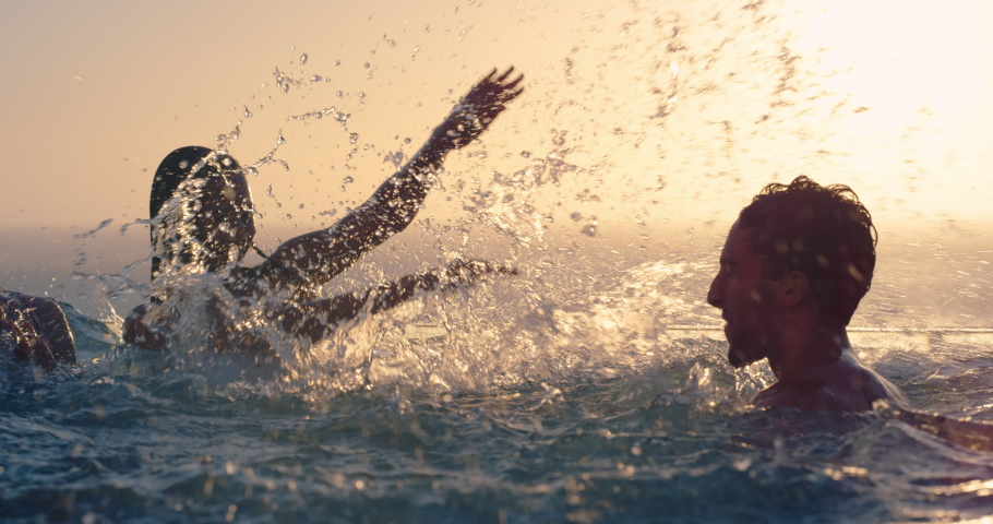 Friends swimming in pool splashing playfully enjoying summer vacation having fun celebrating summertime holiday at luxury hotel with ocean view sunset 4k | Shutterstock HD Video #1034496575