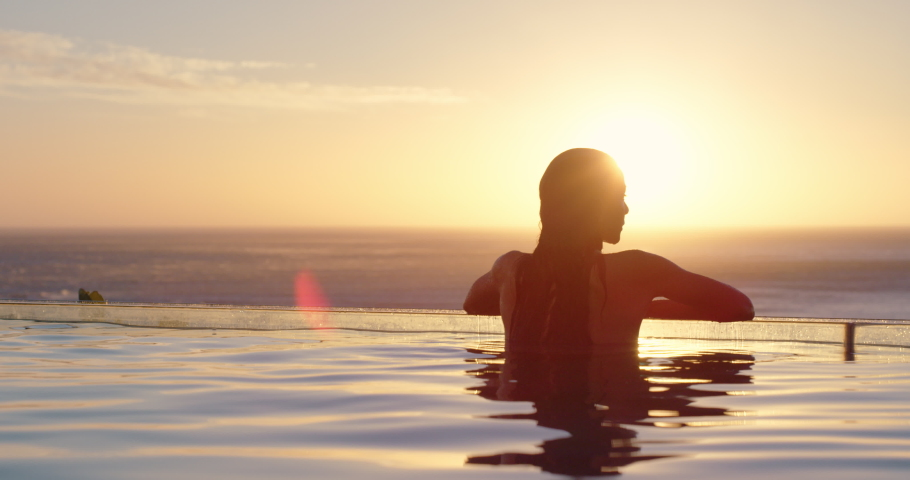 Woman relaxing in swimming pool at luxury hotel spa enjoying beautiful sunset view of ocean mediterranean travel holiday resort 4k | Shutterstock HD Video #1034496914
