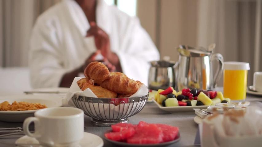 Cinematic African American Man Eating Fruit At Breakfast In Hotel Room.