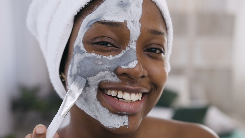 Close-up of smiling afro-american girl with towel on the head applying a cleansing clay mask on face, using make up brush while looking at camera on the white background.