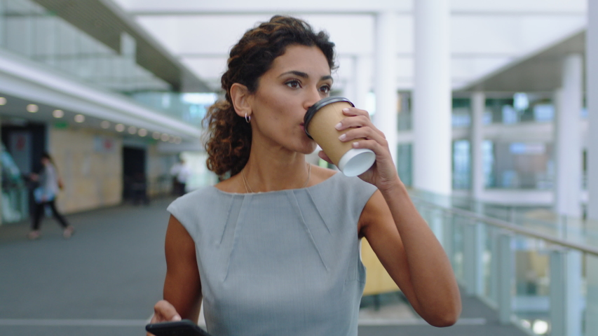hispanic business woman in airport walking using smartphone texting in corporate office typing text messages on mobile phone drinking coffee successful female executive at work 4k footage #1034502959