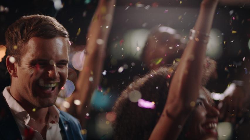 new years eve friends celebrating rooftop party dancing throwing confetti enjoying glamorous celebration wearing stylish fashion social gathering at night 4k #1034504246