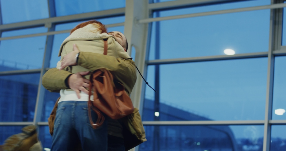 Caucasian young good looking happy and cheerful boyfriend and girlfriend meeting and hugging in the airport or train station.