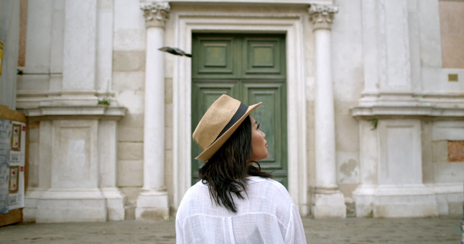 Woman traveller in front of massive antique door from behind in fedora in historic Venice Italy | Shutterstock HD Video #1034515280