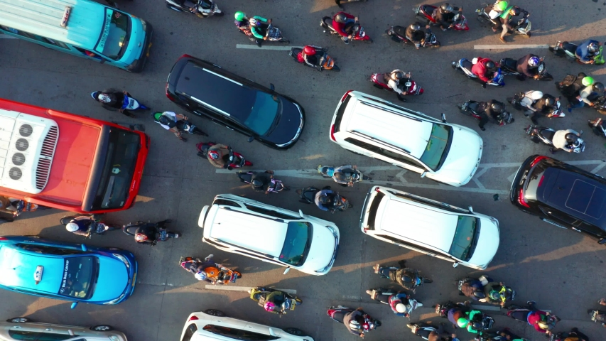 JAKARTA, Indonesia - July 30, 2019: Top down view cars and motorcycle moving on traffic jam at rush hour in Jakarta city. Shot in 4k resolution from a drone flying upwards