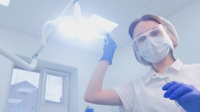 Portrait of dentist woman holds dental tools and looks at camera ready to work, first person video. Oral hygiene and dental treatment cure in dentistry. Stomatologist in stomatology clinic.