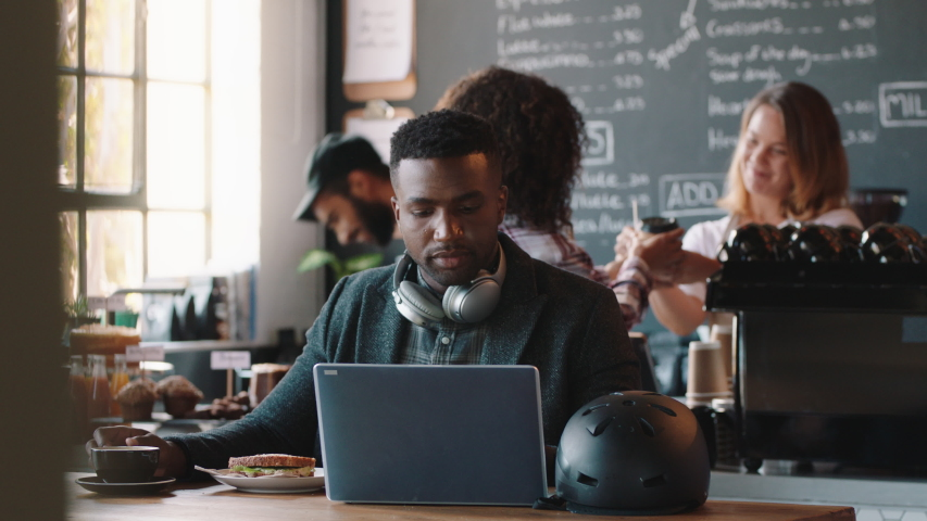young african american man using laptop in cafe browsing online listening to music wearing headphones enjoying mobile computer technology Royalty-Free Stock Footage #1034534399