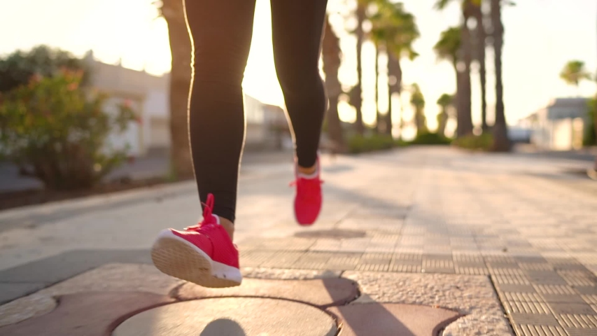 Close up of legs of a woman running along the palm avenue at sunset. Slow motion #1034538995