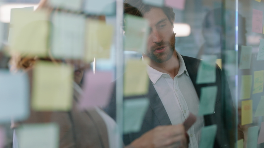 business people using sticky notes on glass whiteboard brainstorming team leader woman working with colleagues showing problem solving strategy in office meeting 4k Royalty-Free Stock Footage #1034541152