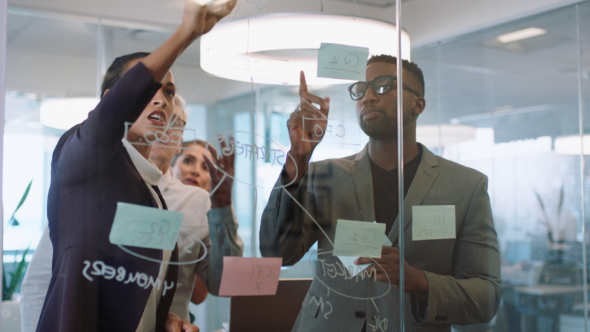 business people using sticky notes brainstorming team leader woman writing on glass whiteboard working with colleagues showing problem solving strategy in office meeting