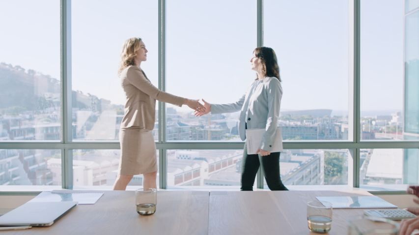 Business women shaking hands in boardroom meeting successful corporate partnership deal with handshake colleagues clapping hands welcoming opportunity for cooperation in office 4k | Shutterstock HD Video #1034542847