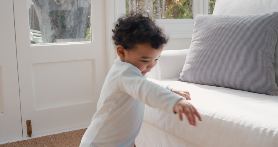 Happy baby learning to walk smiling toddler having fun taking first steps walking enjoying childhood curiosity 4k   Shutterstock HD Video #1034550230