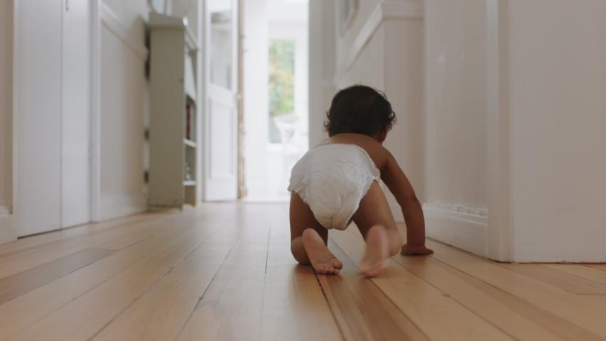 baby girl crawling on floor toddler exploring home curious infant having fun enjoying childhood #1034551097
