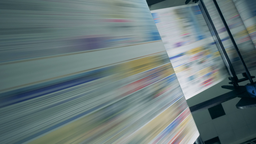 Long newspaper pages moving on a conveyor at a printing office. Royalty-Free Stock Footage #1034551595