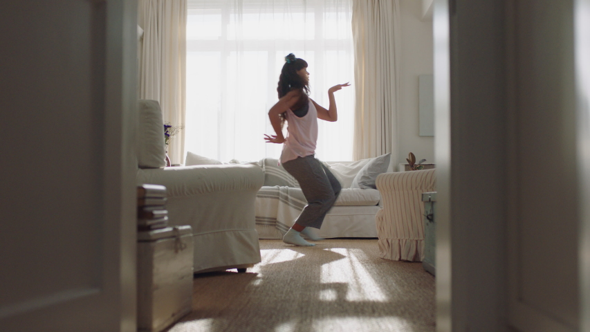 happy young woman dancing at home having fun celebrating with funny dance moves enjoying freedom on weekend morning 4k footage #1034555060