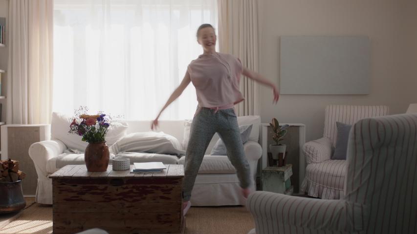 happy teenage girl dancing at home having fun celebrating weekend with funny dance moves playful teen enjoying freedom 4k footage #1034555102