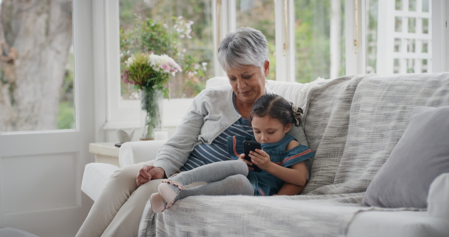 Adorable little girl showing grandmother how to use smartphone teaching granny modern technology intelligent child helping grandma with mobile phone at home 4k | Shutterstock HD Video #1034557259