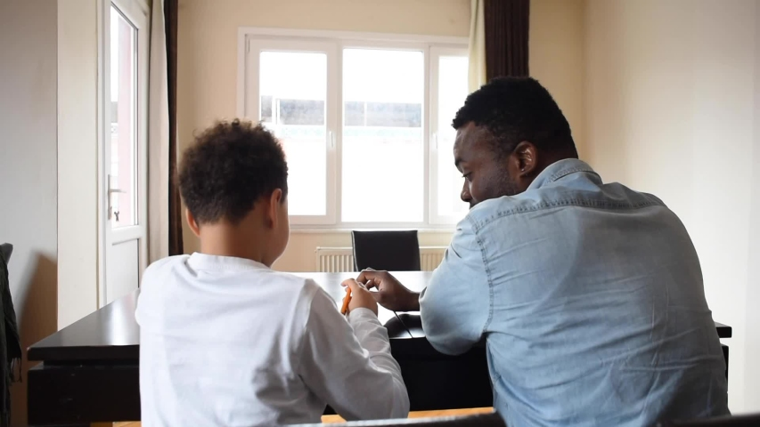 Father and son do homework at home. Tutor teaches the boy at home. Home schooling. African american teacher and mixed boy. #1034569133