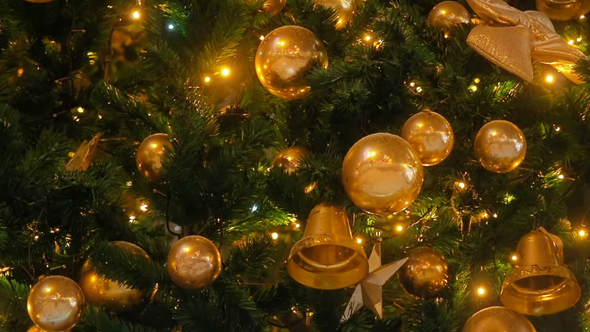 Close up a Christmas tree lights glittering at night. New Year fir tree with decorations and illumination. Xmas tree decorations background. Many large golden balls on fir tree New Year and Christmas | Shutterstock HD Video #1034570159