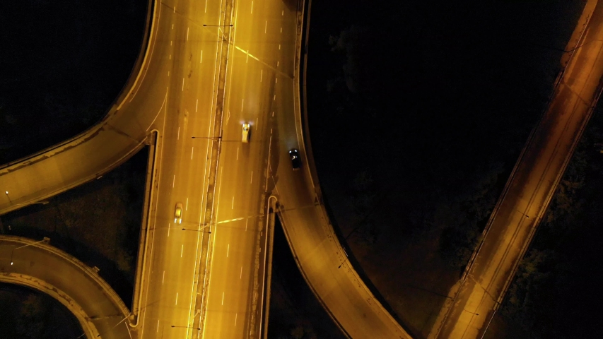Highway cloverleaf interchange intersection (junction) with ramps, heavy traffic, aerial hyperlapse. A cloverleaf typical two-level, four-way interchange.   Shutterstock HD Video #1034570774