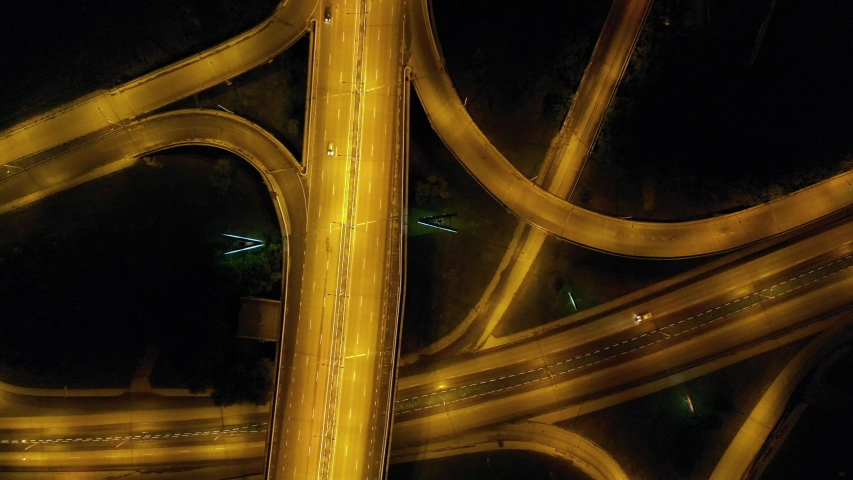 Rising drone shot reveals spectacular elevated highway and convergence of roads, bridges, viaducts in city at night, transportation and infrastructure development in urban area. | Shutterstock HD Video #1034570777