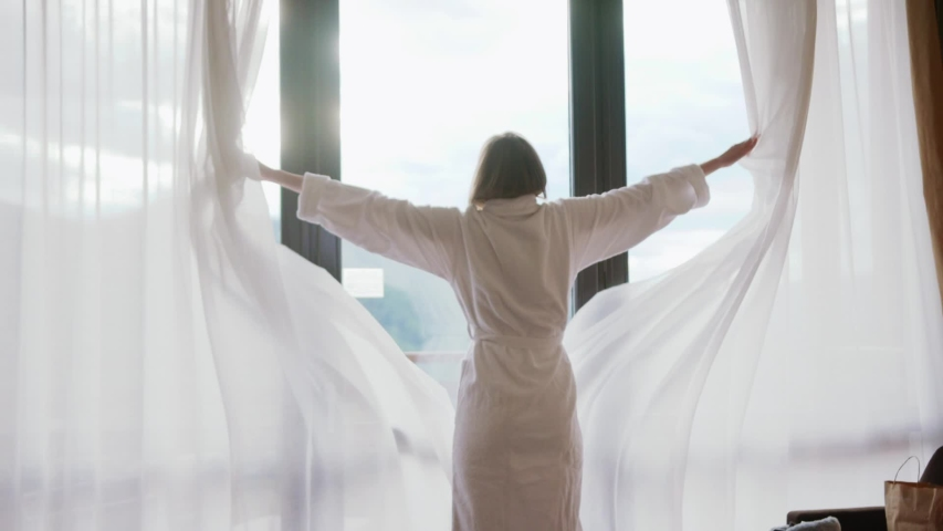 Close up back view young woman opening curtain lace standing in luxury apartment home or hotel looking through window enjoying wellbeing light city skyscrapers morning close up slow motion