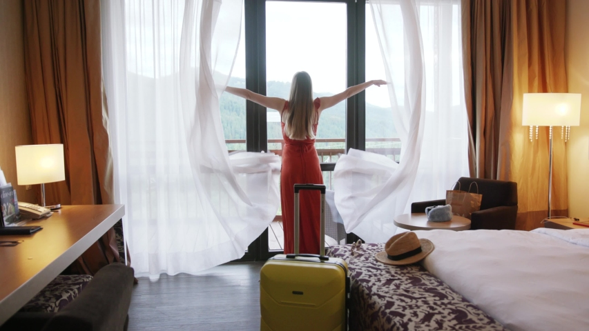 Shot back young woman is entering opening curtain lace hands raise standing in luxury apartment inspecting space feel happy apartment tourist trip holiday close up slow motion