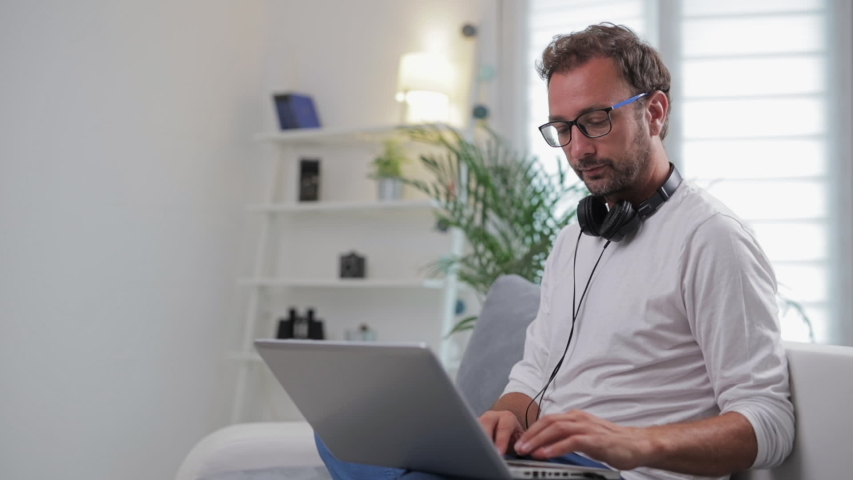 Man listening to music and using laptop in the living room. #1034582306