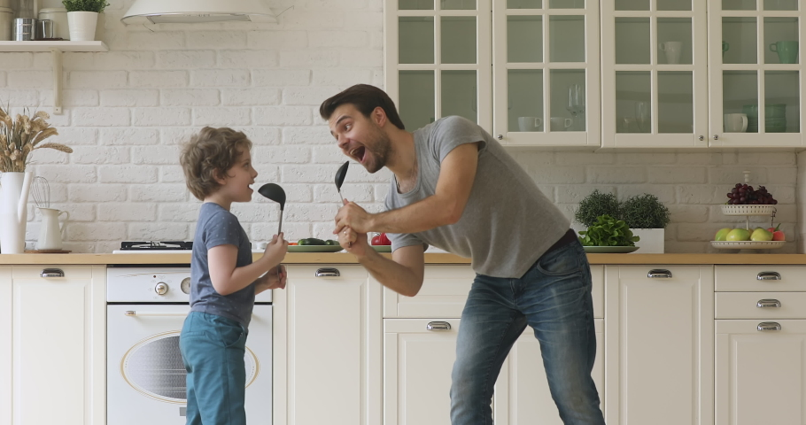 Funny artistic father and cute little kid son singing song in kitchen, happy family dad with child boy holding spoon ladle kitchenware microphones enjoy karaoke dancing having fun in kitchen together Royalty-Free Stock Footage #1034586188
