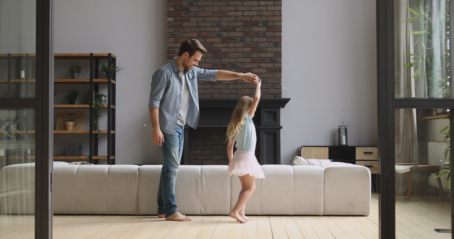 Loving young dad stand on knee holding kissing hand dancing with cute little child daughter princess in modern living room, happy father and small kid girl playing enjoy sweet time together at home