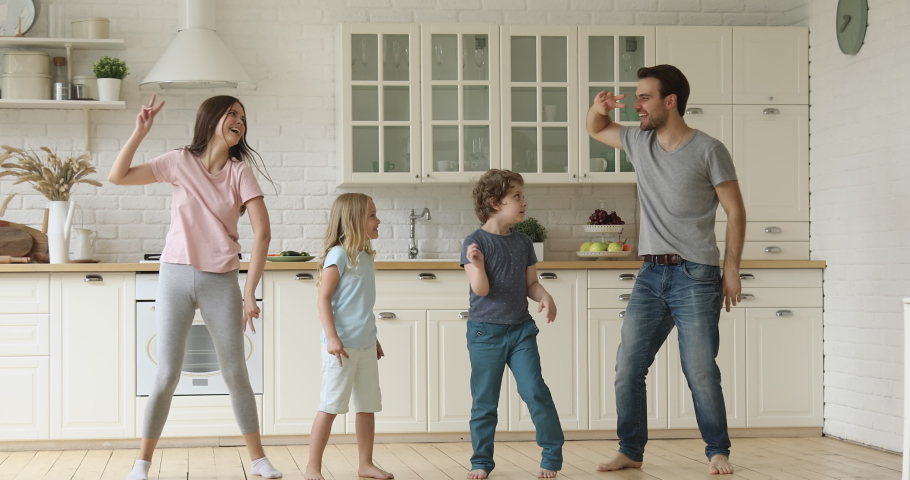 Funny happy family and cute children siblings having fun dancing in kitchen together, active mom dad enjoying funky dance with kids son daughter copy imitate fit sporty young parents laughing at home | Shutterstock HD Video #1034586209