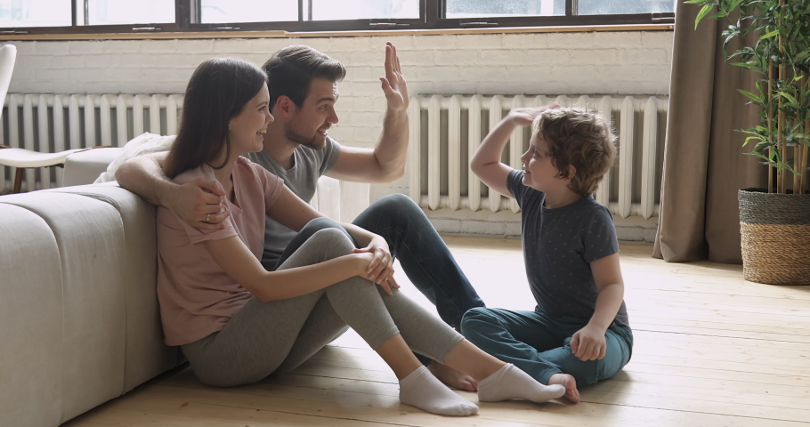 Happy family of three young parents and little child son talking sit on floor at home, loving dad speaking giving high five to preschool cute small kid boy having fun playing bonding together in livin