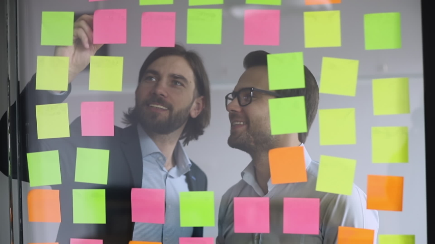 Two happy businessmen colleagues team write on post it sticky notes look at glass wall scrum board brainstorm on work organization task management discuss strategy plan in office at teamwork meeting