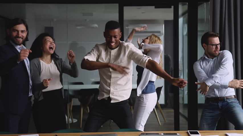Motivated funny diverse business team people dancing celebrating success at corporate party on friday, happy friendly multiracial coworkers group having fun together enjoy victory dance in office | Shutterstock HD Video #1034587586