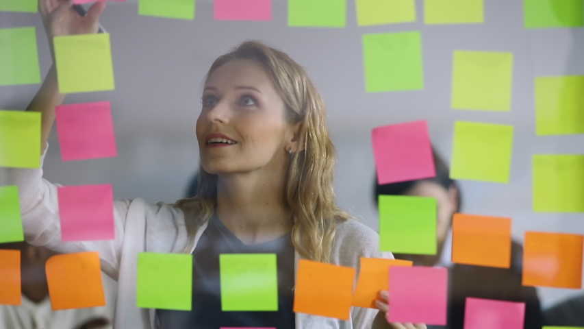 Young businesswoman office worker replacing sticky notes on planning board, female corporate leader write project tasks on post it sticky notes organize work attaching stickers on scrum glass wall