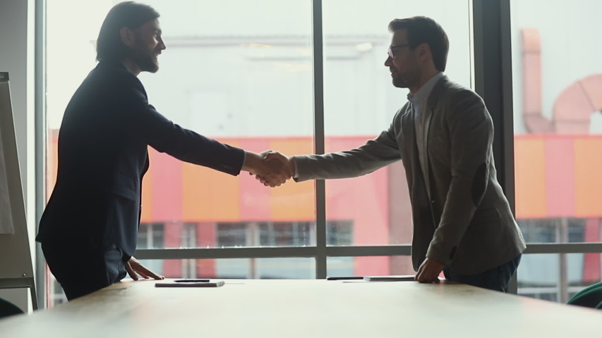 Two businessmen negotiators wear suits shake hands after successful negotiations, seller banker handshake partner client investor make investment partnership deal agreement trust concept, side view