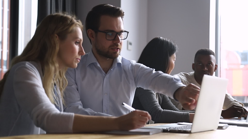 Helpful experienced male boss mentor teacher instructing young female intern trainee new worker making notes explaining new online project looking at laptop computer at apprentice course in office Royalty-Free Stock Footage #1034587652