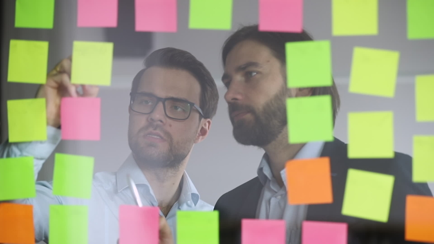 Two focused male colleagues partners team writing business ideas on paper post it sticky notes on glass wall discussing teamwork brainstorm on strategy work plan in corporate office at scrum meeting