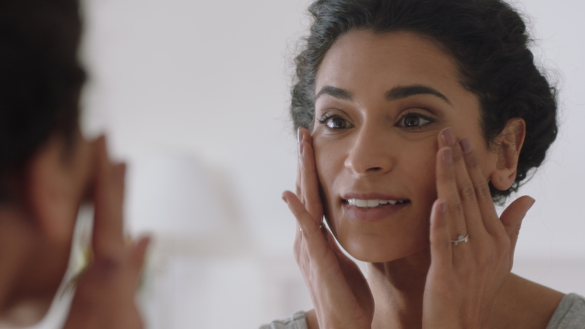 Portrait beautiful young woman looking in mirror at perfect healthy skin touching face with hands enjoying smooth natural complexion with anti aging skincare getting ready at home beauty concept | Shutterstock HD Video #1034590814