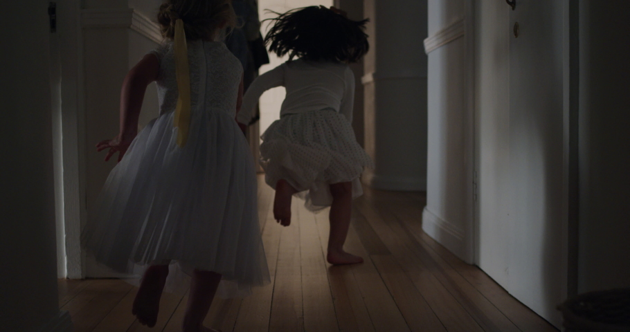 happy little girls running through house playing game of catch wearing tutu excited children enjoying childhood fun on weekend morning 4k #1034590916