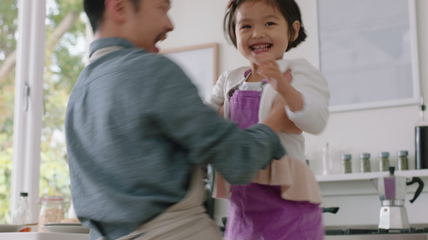 happy asian family dancing in kitchen father enjoying dance with daughter little girl laughing enjoying exciting weekend at home 4k footage #1034594174