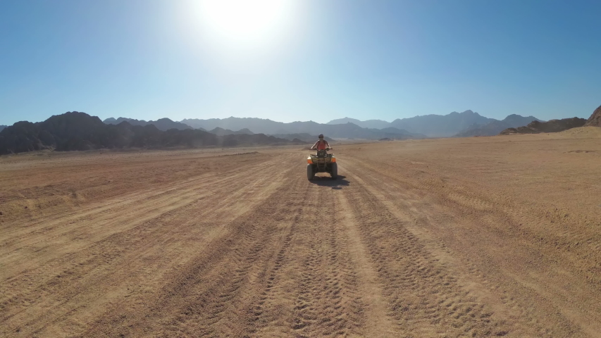 Sexy Woman is Riding a Quad Bike in the Desert of Egypt. Rides ATV bike through the desert. Dynamic view in motion. Adventures of desert off-road on ATVs. Sharm el Sheikh. | Shutterstock HD Video #1034596718