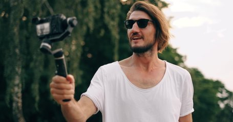 Young attractive bearded man blogger or vlogger recording video movie and looking at camera and talking on video shooting. Social media influencer people or content maker concept in relax at nature.