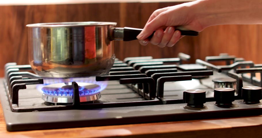 Woman puts a metal bucket on a stove. Food cooking in small pan with shiny side on open fire gas stove | Shutterstock HD Video #1034602952