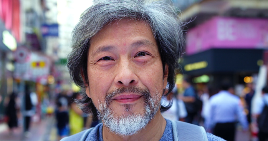 Portrait of older trendy asian man at camera in the street of causeway bay Honk Kong. Slow motion, hand held, Shot on red. Note: no visible faces in background, blurred faces.
