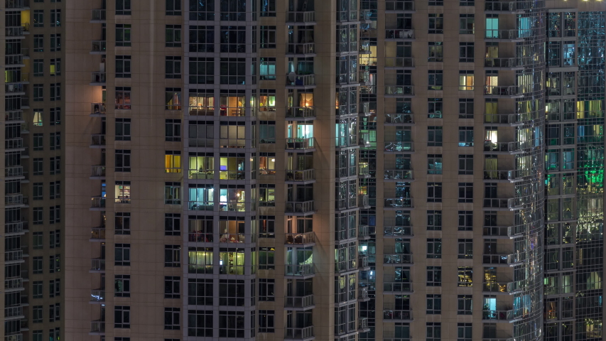 Windows of the multi-storey building with lighting inside and moving people in apartments timelapse. Aerial view of modern residential skyscrapers in Dubai downtown. Zoom in | Shutterstock HD Video #1034630705