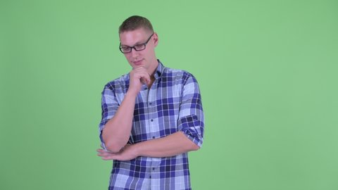Stressed young hipster man with eyeglasses thinking and looking down